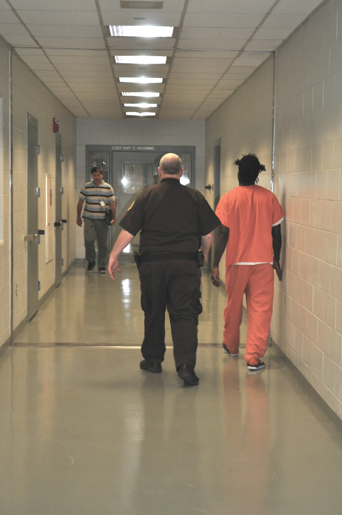 Officer and Inmates in Jail Hallway